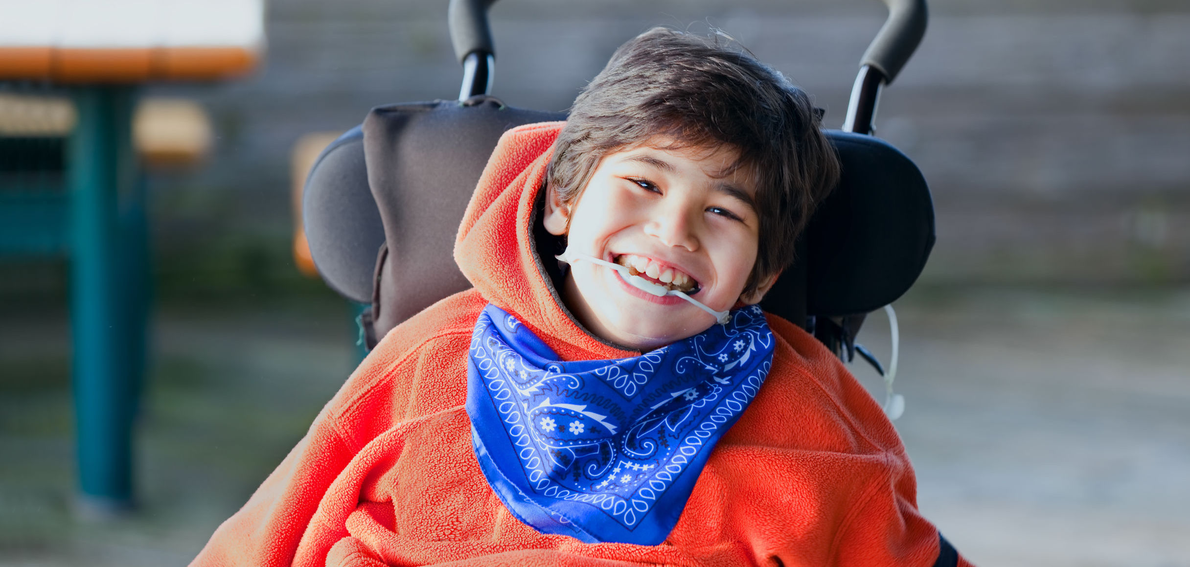 boy smiling in wheelchair outdoors