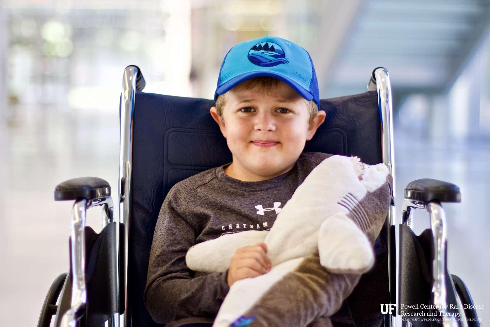 Boy wearing a blue hat sitting in a wheel chair holding stuffed shark